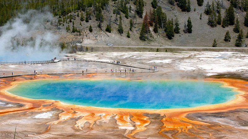 Yellowstone grand prismatic pool with people hiking